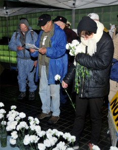 World War II veteran Jay Wenk tolls a bell while Vietnam veteran Tarak Kauff reads the names of the fallen moments before their arrest on October 7, 2012.